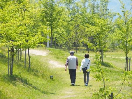 温かい日差しのもとで散歩をする老夫婦