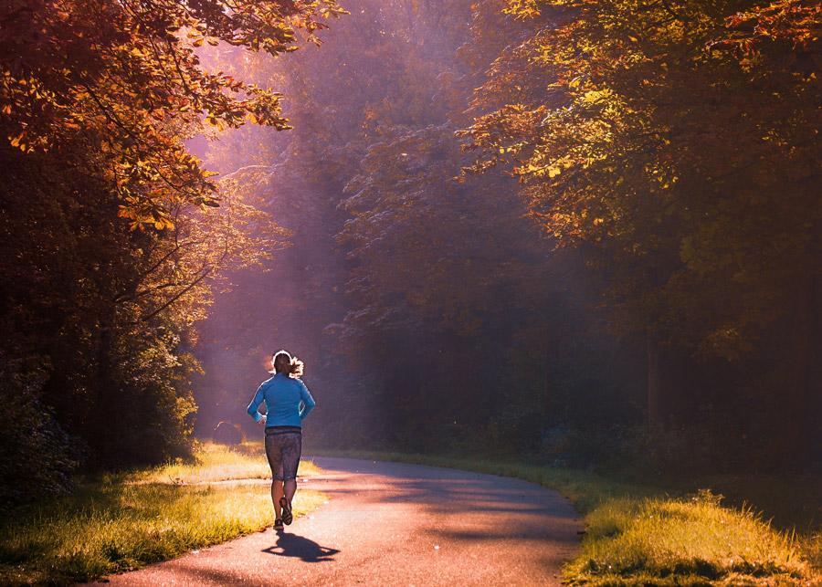朝日を浴びながら走る女性