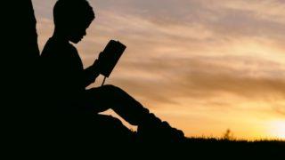 木にもたれかかって本を読む少年