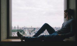 一人で寂しそうにする男性の画像